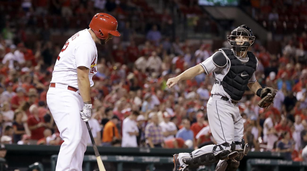 Miami Marlins catcher J.T. Realmuto, right, heads toward the mound after St. Louis Cardinals' Matt Adams struck out to end a baseball game Friday, July 15, 2016, in St. Louis. The Marlins won 7-6. (AP Photo/Jeff Roberson)