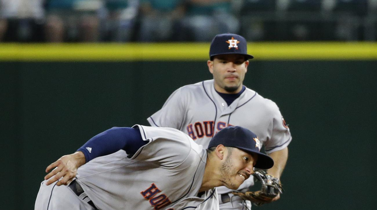 Houston Astros shortstop Carlos Correa, left, catches a ball hit by Seattle Mariners' Adam Lind for an out during the sixth inning of a baseball game Friday, July 15, 2016, in Seattle. (AP Photo/Ted S. Warren)