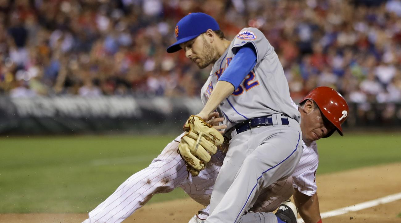 Philadelphia Phillies' Carlos Ruiz, rear, scores past New York Mets relief pitcher Erik Goeddel on a wild pitch during the eighth inning of a baseball game Saturday, July 16, 2016, in Philadelphia. Philadelphia won 4-2. (AP Photo/Matt Slocum)