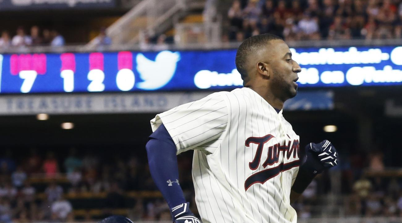 Minnesota Twins' Eduardo Nunez loses his helmet as he races home to score on an error by Cleveland Indians first baseman Carlos Santana during the seventh inning of a baseball game Saturday, July 16, 2016, in Minneapolis. (AP Photo/Jim Mone)