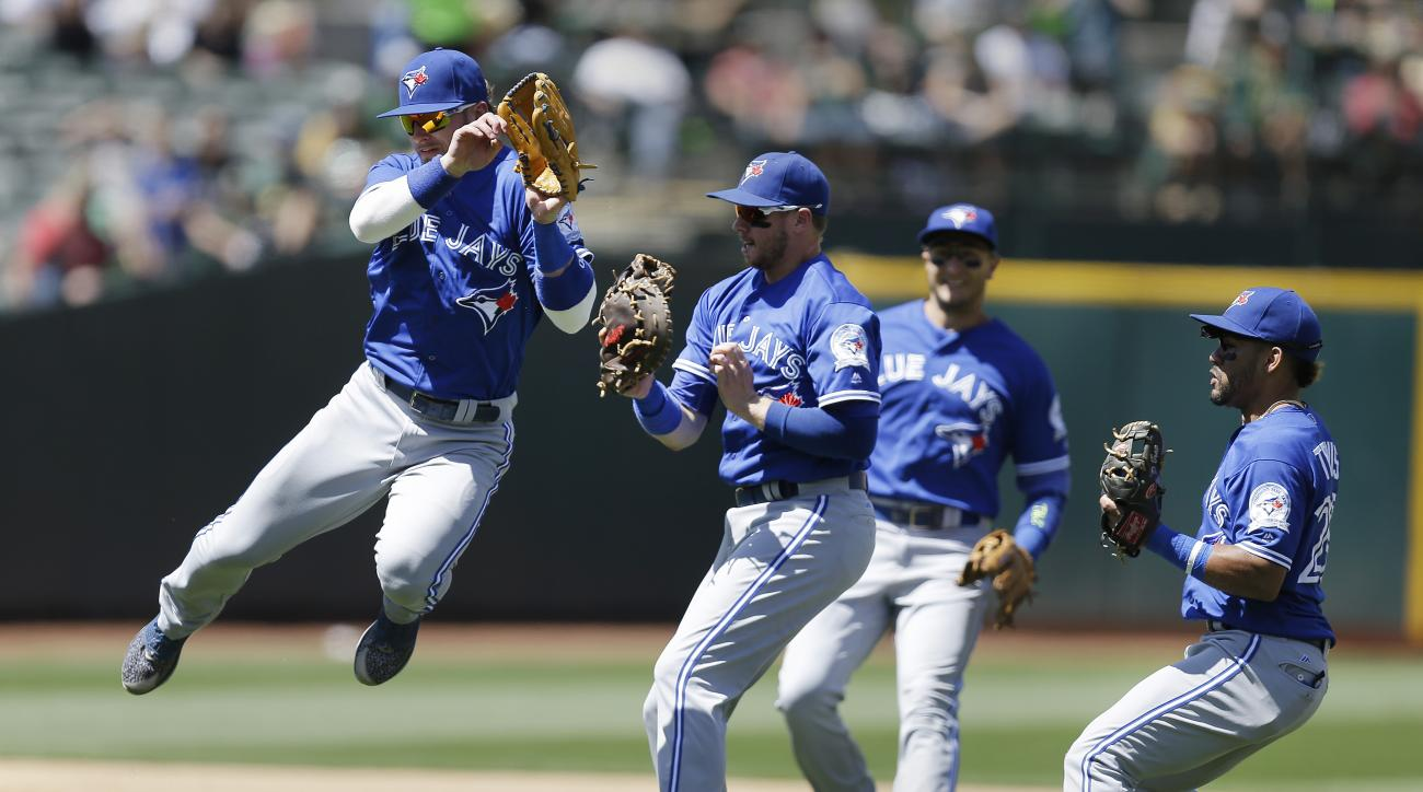 Toronto Blue Jays' Josh Donaldson, left, avoids a collision with Justin Smoak, second from left, after Smoak caught a ball hit by Oakland Athletics' Matt McBride in the sixth inning of a baseball game Sunday, July 17, 2016, in Oakland, Calif. (AP Photo/Be