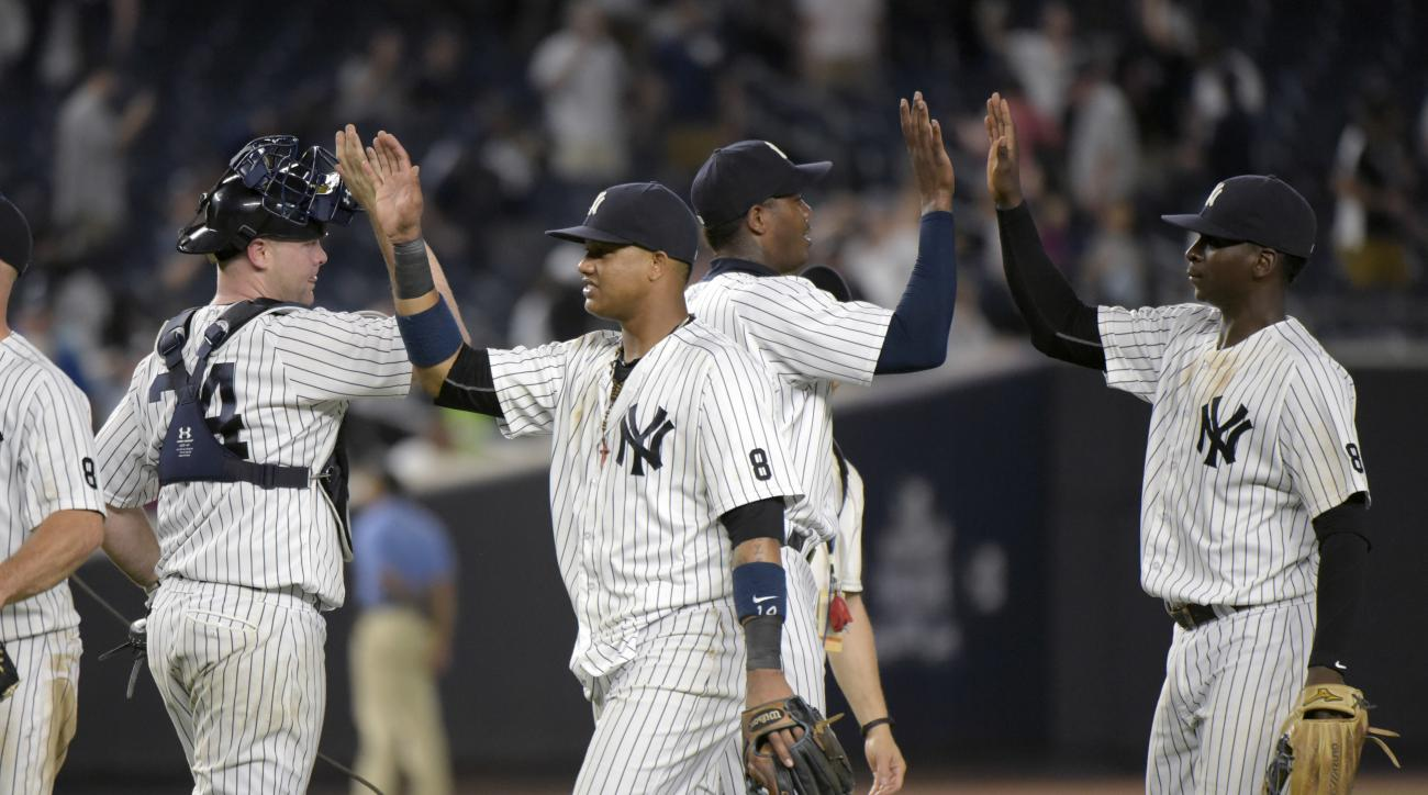 From left, New York Yankees Brian McCann, Starlin Castro, Aroldis Chapman and Didi Gregorius celebrate after the Yankees defeated the Baltimore Orioles, 2-1, in a baseball game Monday, July 18, 2016, at Yankee Stadium in New York. (AP Photo/Bill Kostroun)