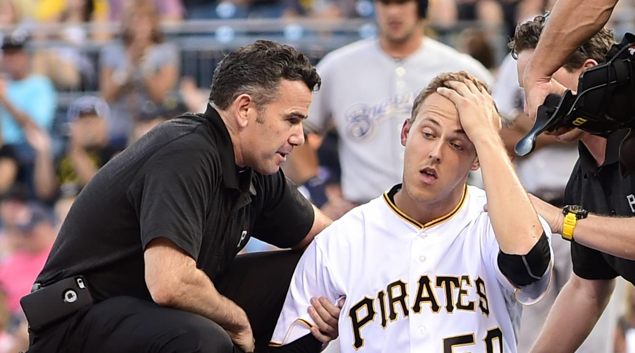 Athletic trainer Ben Potenziano, left, watches Pittsburgh Pirates starting pitcher Jameson Taillon (50) hold his head in the second inning of a baseball game against the Milwaukee Brewers in Pittsburgh, Tuesday, July 19, 2016. Taillon was hit by a ball of