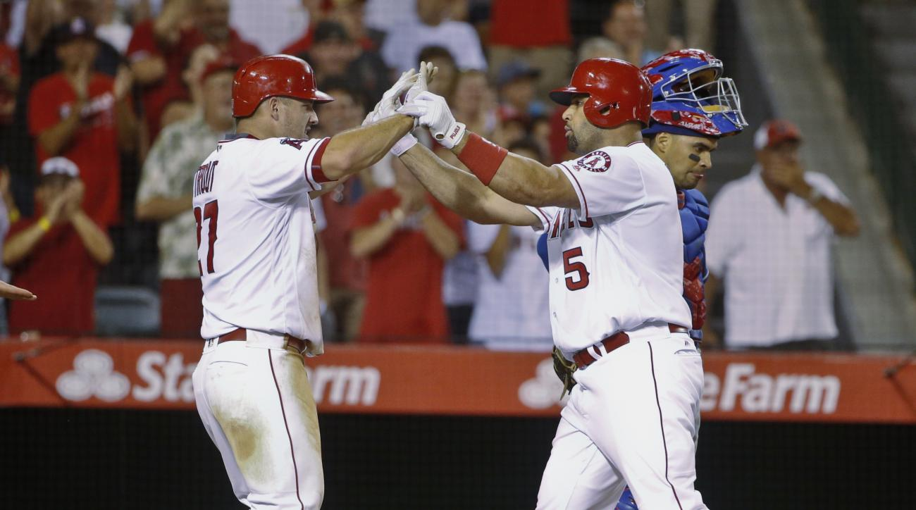 Los Angeles Angels' Albert Pujols is congratulated by Mike Trout after hitting his second three run homer against the Texas Rangers in the fifth inning of a baseball game Tuesday, July 19, 2016, in Anaheim, Calif. (AP Photo/Lenny Ignelzi)