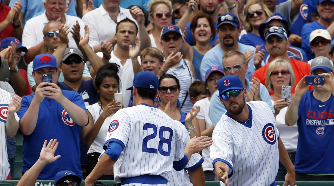 Chicago Cubs starter Kyle Hendricks (28) celebrates with teammates as he leaves the mound during the seventh inning of a baseball game against the New York Mets Wednesday, July 20, 2015, in Chicago. (AP Photo/Nam Y. Huh)