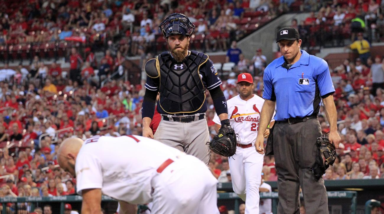 San Diego Padres catcher Derek Norris and home plate umpire Chris Guccione, right, watch and St. Louis Cardinals manager Mike Matheny, second from right, comes running as Cardinals' Matt Holliday, left, doubles over after being hit in the face by a pitch