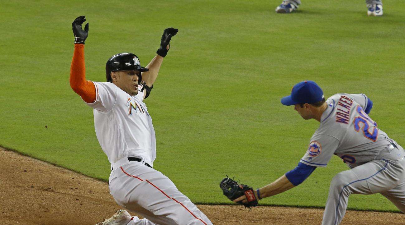 Miami Marlins' Giancarlo Stanton, left is tagged out at second by New York Mets second baseman Neil Walker while trying to stretch a sixth-inning single during a baseball game in Miami, Friday, July 22, 2016. (AP Photo/Joe Skipper)