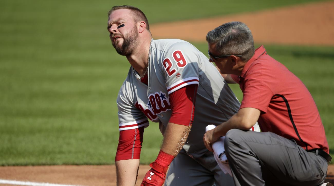 Philadelphia Phillies' Cameron Rupp, left, is helped by a team trainer after being hit on the batting helmet by a pitch from Pittsburgh Pirates starter Tyler Glasnow in the third inning of a baseball game in Pittsburgh, Saturday, July 23, 2016. Rupp left