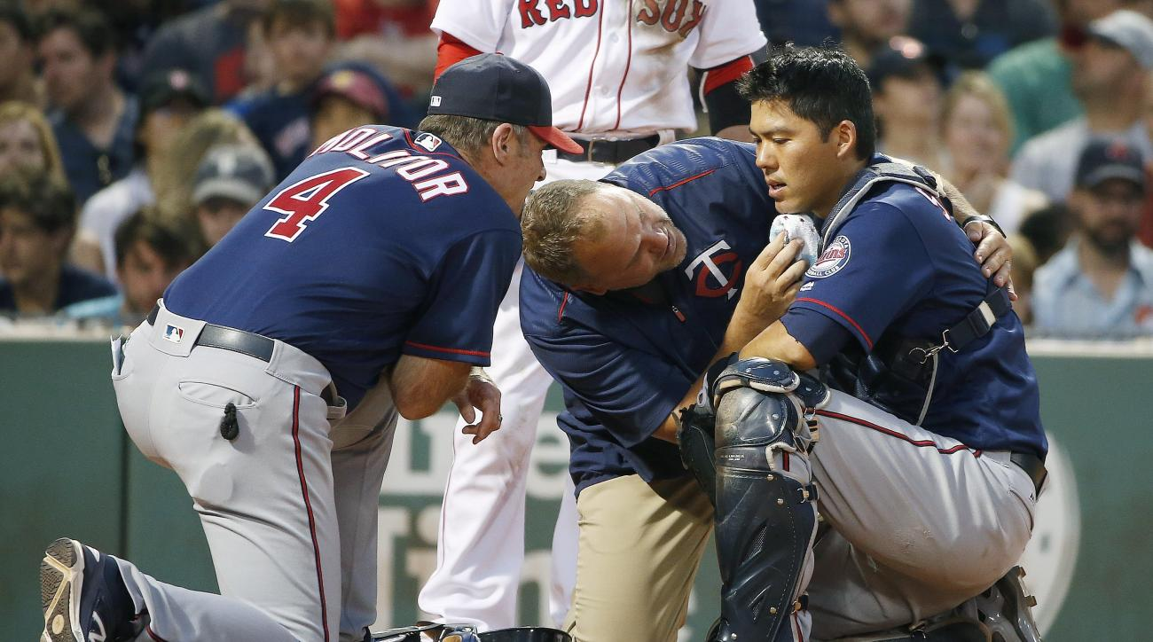 Minnesota Twins manager Paul Molitor (4) and a trainer tend to Kurt Suzuki, right, who was injured on a pitch during the second inning of a baseball game against the Boston Red Sox in Boston, Saturday, July 23, 2016. Suzuki left the game. (AP Photo/Michae
