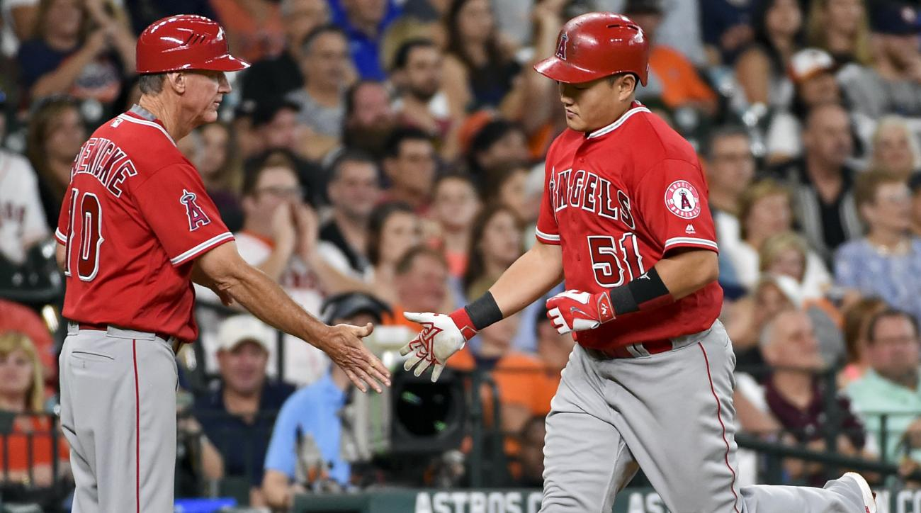 Los Angeles Angels' Ji-Man Choi, right shakes hands with third base coach Ron Ron Roenicke after hitting a solo home run off Houston Astros starting pitcher Collin McHugh (31) in the fifth inning of a baseball game, Saturday, July 23, 2016, in Houston. (A