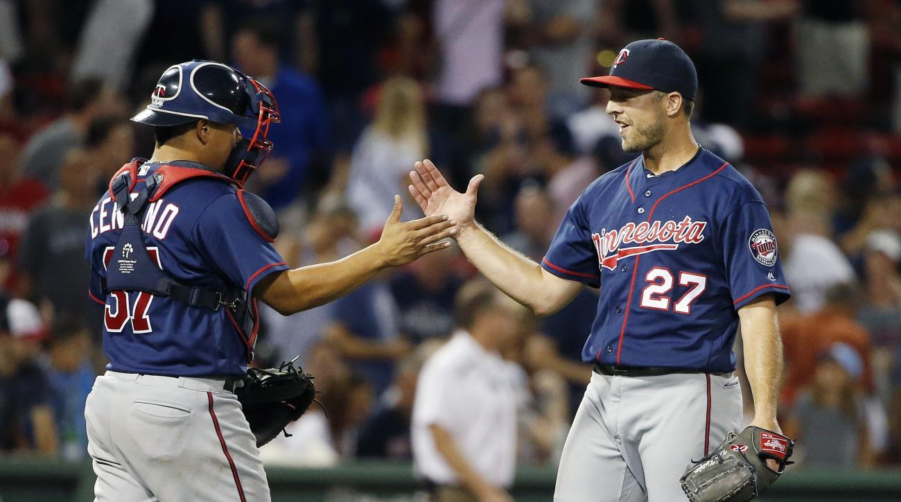 Minnesota Twins' Brandon Kintzler (27) and Juan Centeno (37) celebrate after the Twins defeated the Boston Red Sox 11-9 during a baseball game in Boston, Saturday, July 23, 2016. (AP Photo/Michael Dwyer)
