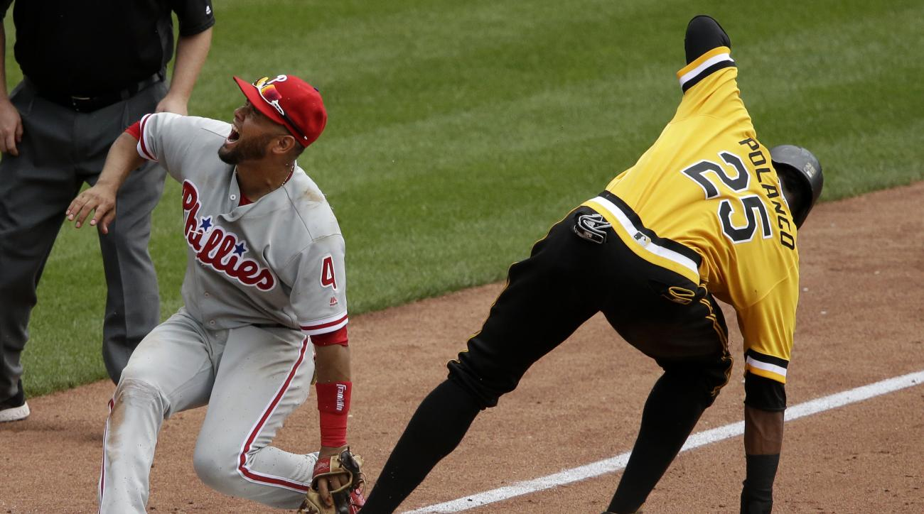 Philadelphia Phillies third baseman Andres Blanco (4) reacts after being spiked on the glove hand while making the tag on Pittsburgh Pirates' Gregory Polanco (25) who was attempting to steal third in the fifth inning of a baseball game in Pittsburgh, Sund