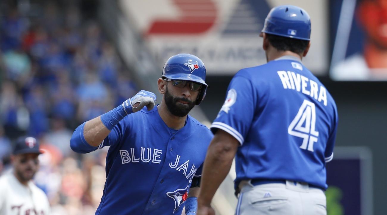 Toronto Blue Jays third base coach Luis Rivera (4) congratulates Jose Bautista, left, as he rounds third after hitting a two-run home run off Minnesota Twins starting pitcher Pat Dean during the third inning of a baseball game in Minneapolis, Saturday, Ma