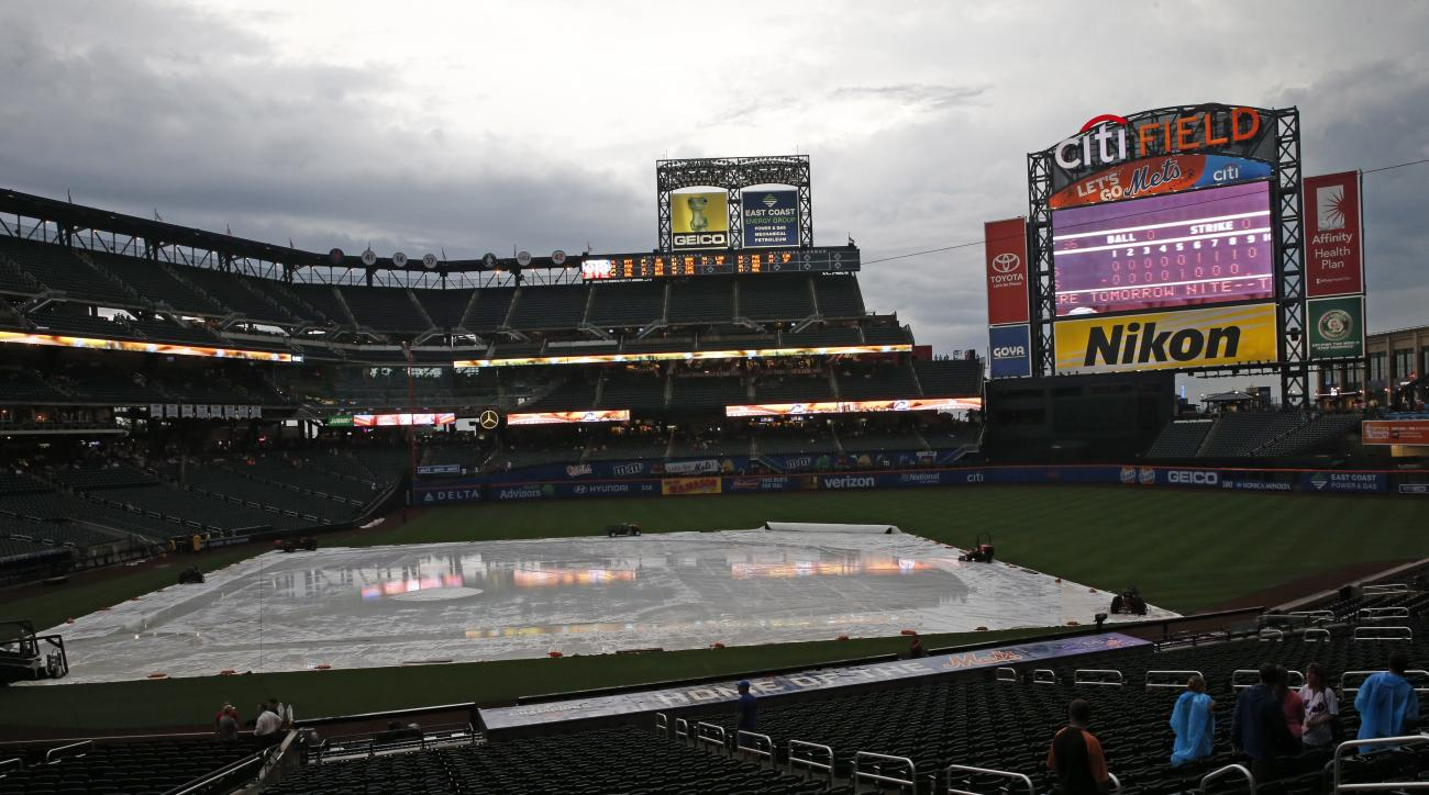 A tarp filled with rain sits on the field before a scheduled baseball game between the St. Louis Cardinals and the New York Mets, Monday, July 25, 2016, in New York. Monday's game was postponed due to rain and will be made up Tuesday as part of a doublehe