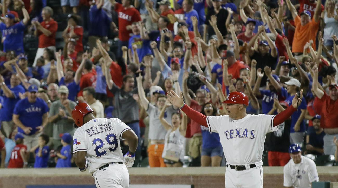 Texas Rangers first base coach Hector Ortiz, right, and fans cheer as Adrian Beltre (29) runs the bases after hitting a game winning two-run homer during the ninth inning of a baseball game against the Oakland Athletics in Arlington, Texas, Monday, July 2