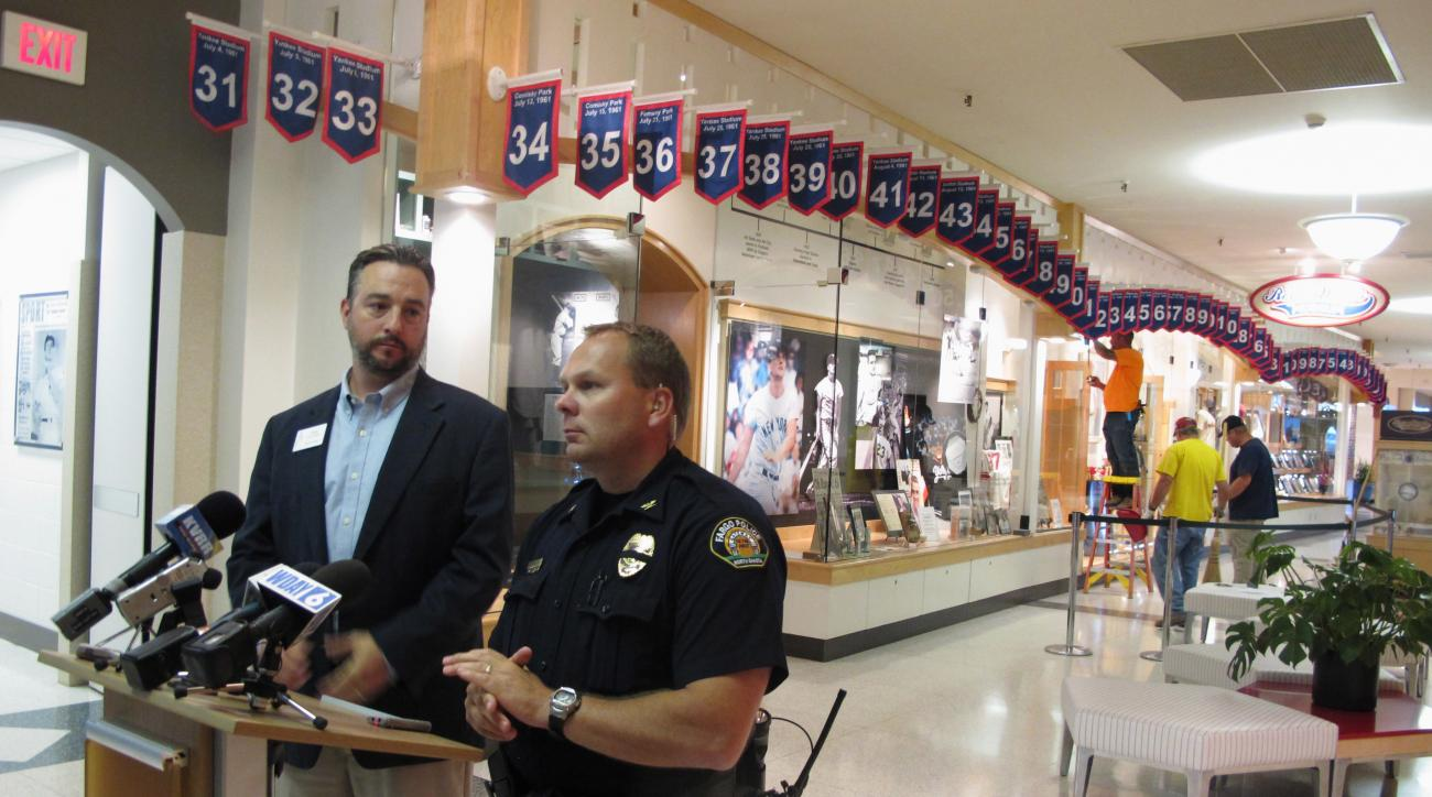 West Acres Mall property manager Chris Heaton, left, and Fargo Deputy Police Chief Joe Anderson talk in front of the Roger Maris Museum in Fargo, N.D., on Tuesday, July 26, 2016, while workers repair a display where an ornate belt was stolen from the mall