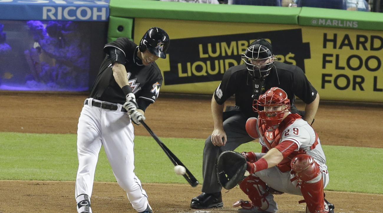 Miami Marlins' Christian Yelich, left, hits a single as Philadelphia Phillies catcher Cameron Rupp watches during the first inning of a baseball game Tuesday, July 26, 2016, in Miami. (AP Photo/Lynne Sladky)