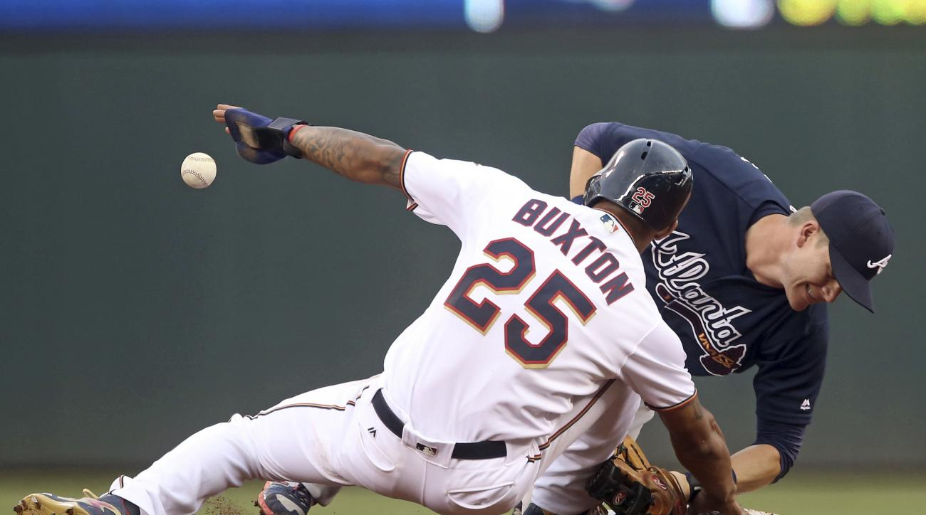Atlanta Braves second baseman Gordon Beckham right, loses the ball as he attempts to tag Minnesota Twins' Byron Buxton off the base as Buxton returned to second after advancing on a single by Eduardo Nunez during the third inning of a baseball game Tuesda