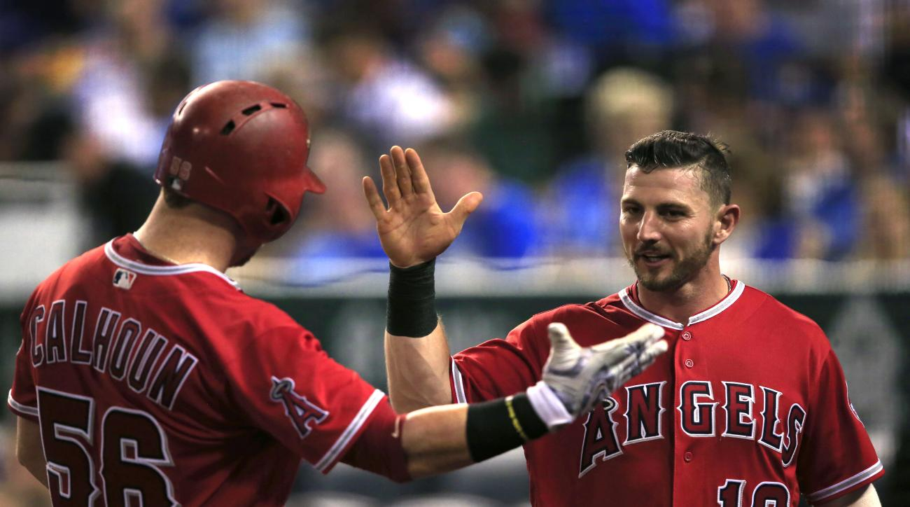 Los Angeles Angels' Johnny Giavotella (12) celebrates with Kole Calhoun (56) during the sixth inning of a baseball game against the Kansas City Royals at Kauffman Stadium in Kansas City, Mo., Tuesday, July 26, 2016. Giavotella scored on a sacrifice fly by