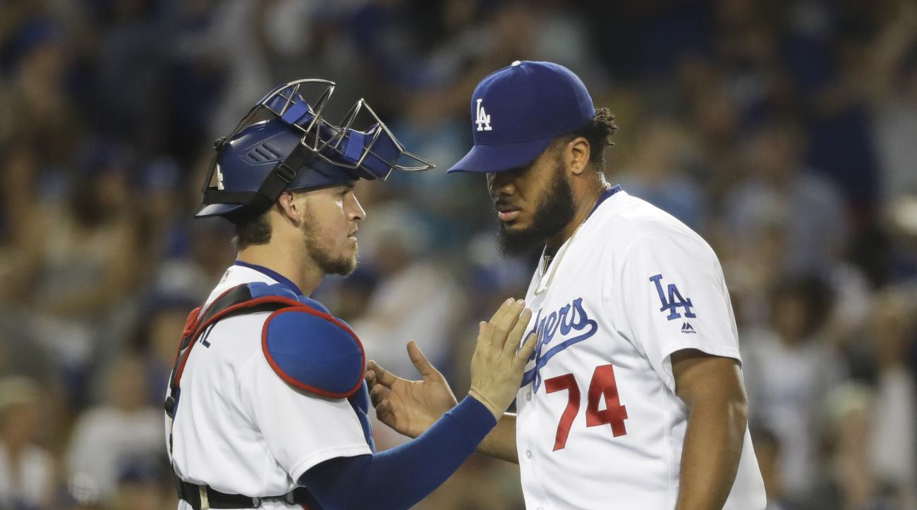 Los Angeles Dodgers relief pitcher Kenley Jansen, right, and catcher Yasmani Grandal shake hands as they celebrate the team's 3-2 win over the Tampa Bay Rays in a baseball game, Tuesday, July 26, 2016, in Los Angeles. (AP Photo/Jae C. Hong)