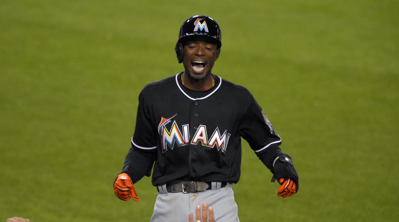 Miami Marlins' Dee Gordon celebrates as he goes into the dugout after scoring on a balk by Los Angeles Dodgers relief pitcher Pedro Baez during the seventh inning of a baseball game, Thursday, April 28, 2016, in Los Angeles. (AP Photo/Mark J. Terrill)