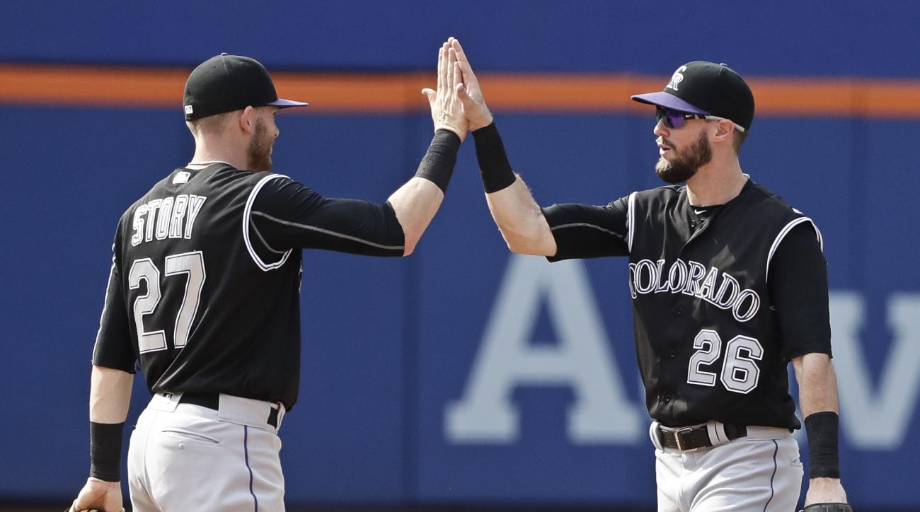 Colorado Rockies' David Dahl (26) and Trevor Story (27) celebrates after a baseball game against the New York Mets Thursday, July 28, 2016, in New York. The Rockies won 2-1. (AP Photo/Frank Franklin II)