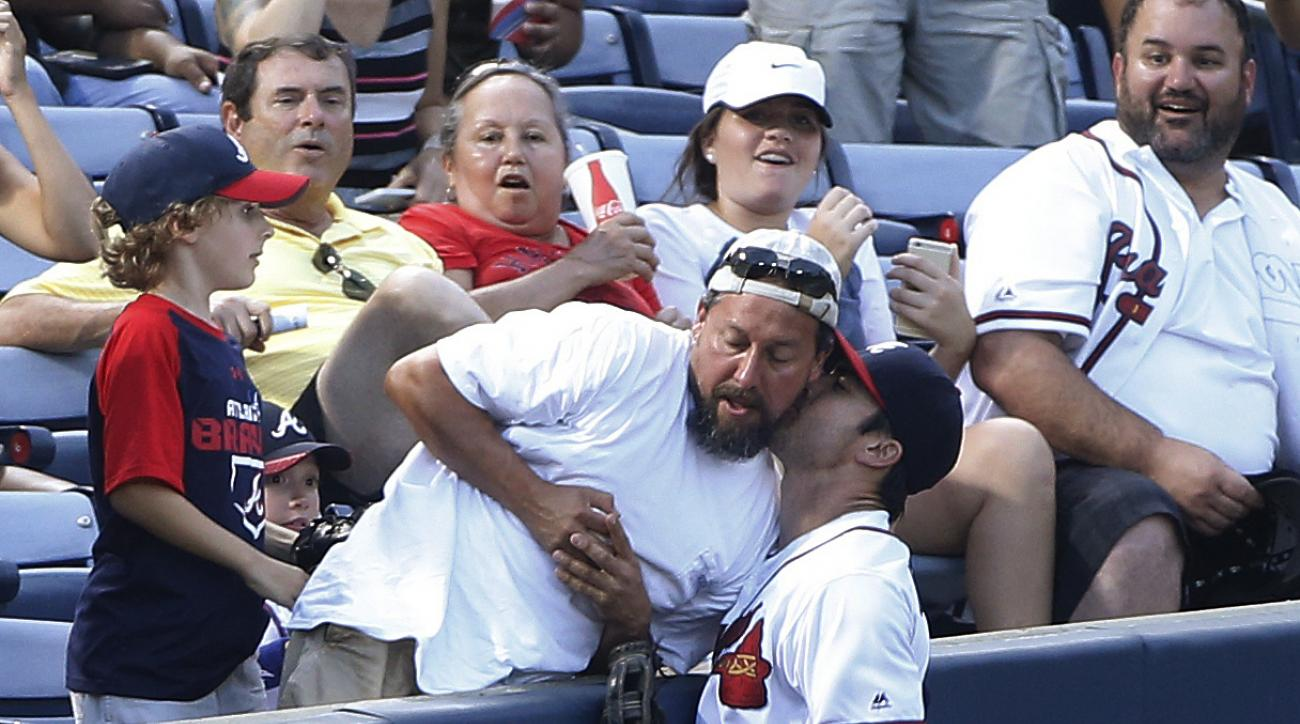 A fan holds on to the ball after catching a foul by Philadelphia Phillies' Cody Asche, while Atlanta Braves left fielder Chase d'Arnaud, right, bumps into the wall and the fan during the fourth inning of a baseball Thursday, July 28, 2016, in Atlanta, Asc