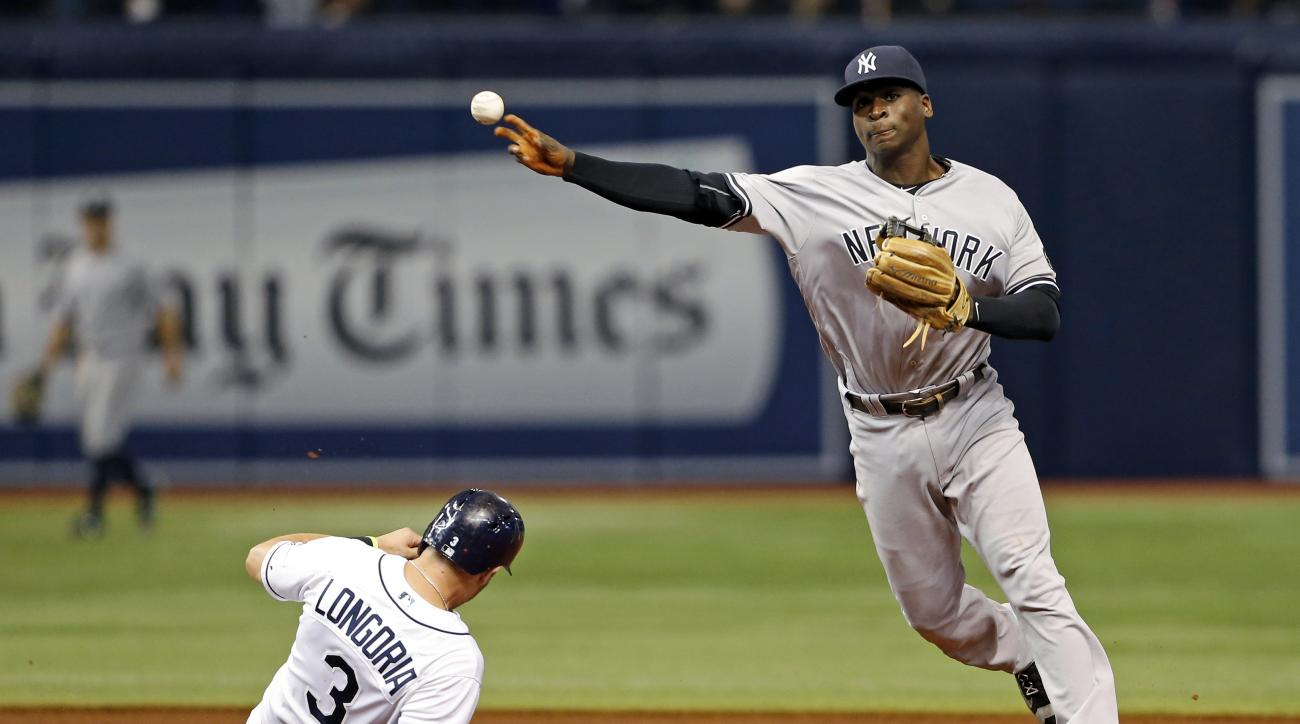 New York Yankees shortstop Didi Gregorius, right, throws wildly over Tampa Bay Rays' Evan Longoria for an error, allowing Brad Miller to score and Corey Dickerson to advance to second, during the third inning of a baseball game Friday, July 29, 2016, in S