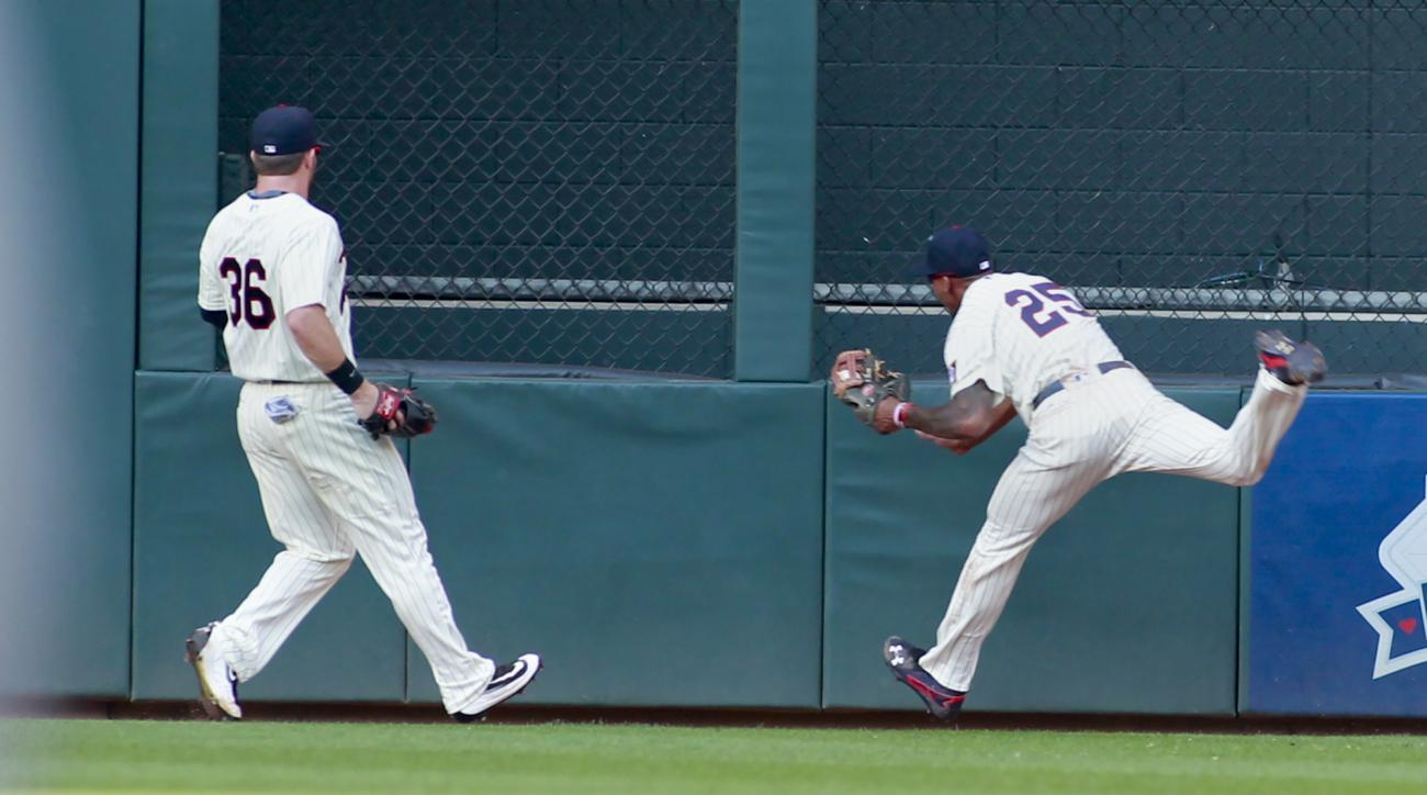 Minnesota Twins center fielder Byron Buxton (25) makes a running catch of a fly ball by Chicago White Sox's Jose Abreu during the fourth inning of an baseball game Saturday, July 30, 2016, in Minneapolis. Twins' Robbie Grossman is at left. (AP Photo/Paul
