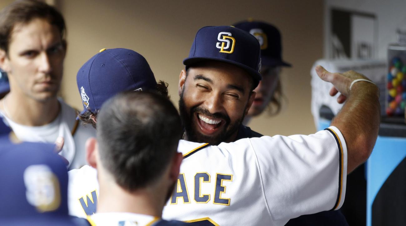 San Diego Padres' Matt Kemp, right, gets a hug from Brett Wallace after making an appearance in the dugout during the first inning of a baseball game against the Cincinnati Reds in San Diego, Saturday, July 30, 2016. (AP Photo/Alex Gallardo)