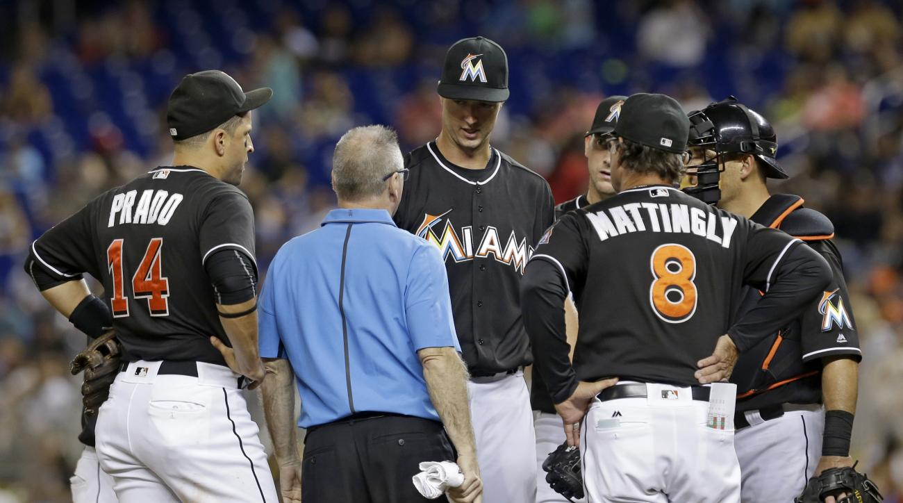Miami Marlins' Colin Rea, third from left, talks manager Don Mattingly (8) in the fourth inning of a baseball game against the St. Louis Cardinals, Saturday, July 30, 2016, in Miami. Rea was relieved by David Phelps. Rea had an elbow injury in his Miami d