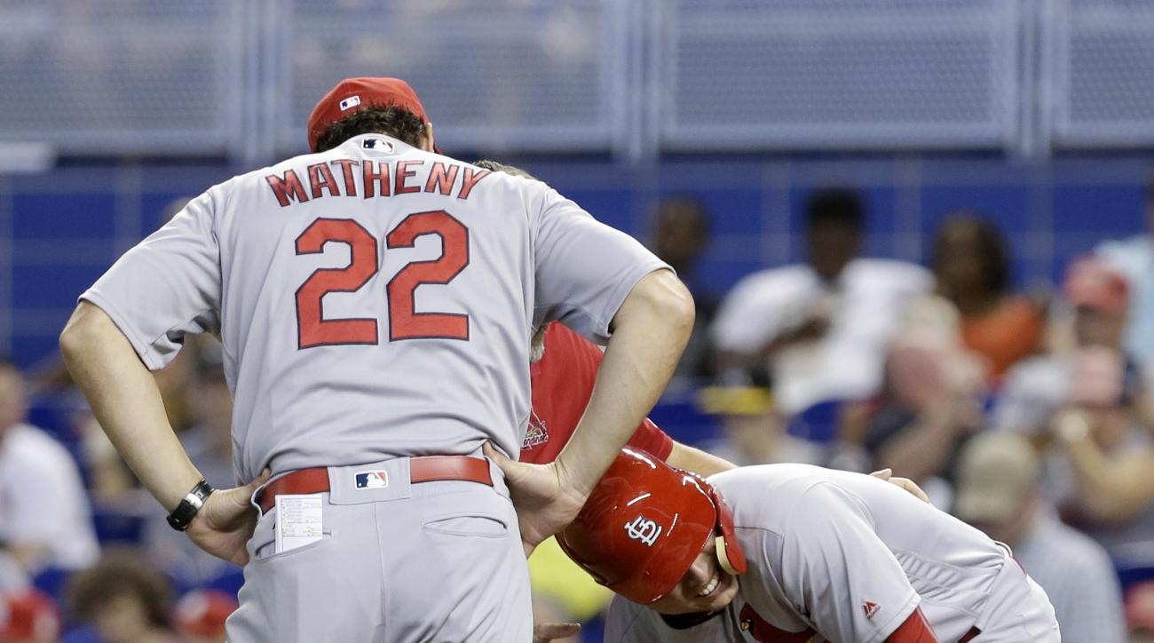St. Louis Cardinals' Aledmys Diaz, right, reacts next to manager Mike Matheny (22) after he was hit by a pitch by Miami Marlins' Andrew Cashner in the first inning of a baseball game Sunday, July 31, 2016, in Miami. (AP Photo/Alan Diaz)