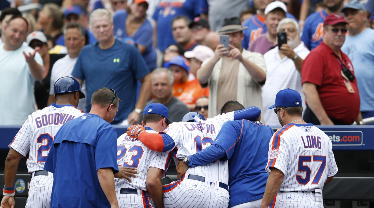 New York Mets first base coach Tom Goodwin, left, bench coach Dick Scott, center, and a team trainer, second from right, help Asdrubal Cabrera off the field after Cabrera doubled over  after scoring on Neil Millers  first-inning RBI-triple during a baseba