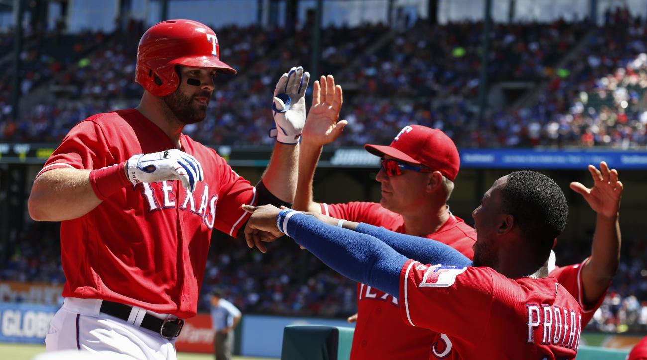 Texas Rangers' Mitch Moreland, left, celebrates his two-run home run with manager Jeff Banister, center, and Jurickson Profar (19) during the fourth inning of a baseball game against the Kansas City Royals, Sunday, July 31, 2016, in Arlington, Texas. (AP