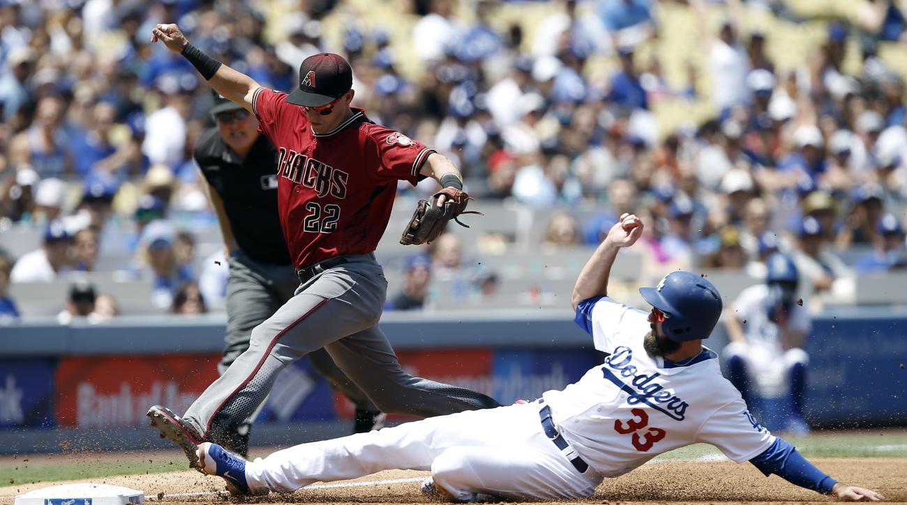 Arizona Diamondbacks third baseman Jake Lamb (22) races to beat Los Angeles Dodgers' Scott Van Slyke (33) to third for the out during the first inning of a baseball game in Los Angeles, Sunday, July 31, 2016. (AP Photo/Alex Gallardo)