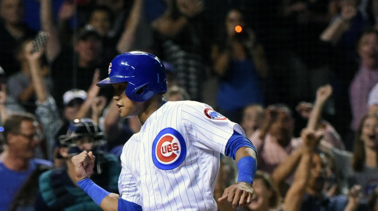 Chicago Cubs Addison Russell pumps his fist as he crosses the plate to tie the game 6-6 during the ninth inning of a baseball game against the Seattle Mariners on Sunday, July 31, 2016, in Chicago. (AP Photo/Matt Marton)