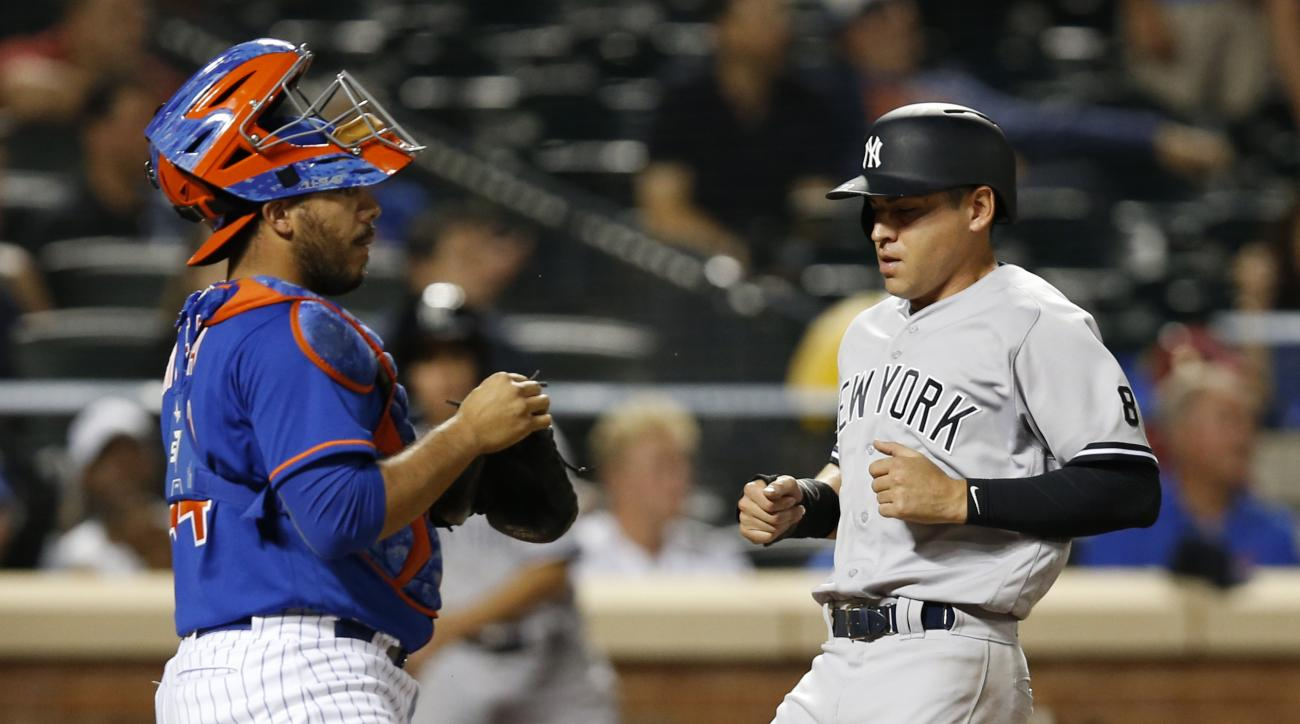 New York Yankees Jacoby Ellsbury (22) scores on Starlin Castro's sacrifice fly in the 10th inning of an interleague baseball game against the New York Mets, Monday, Aug. 1, 2016, in New York. New York Mets catcher Rene Rivera (44) is behind the plate. (AP