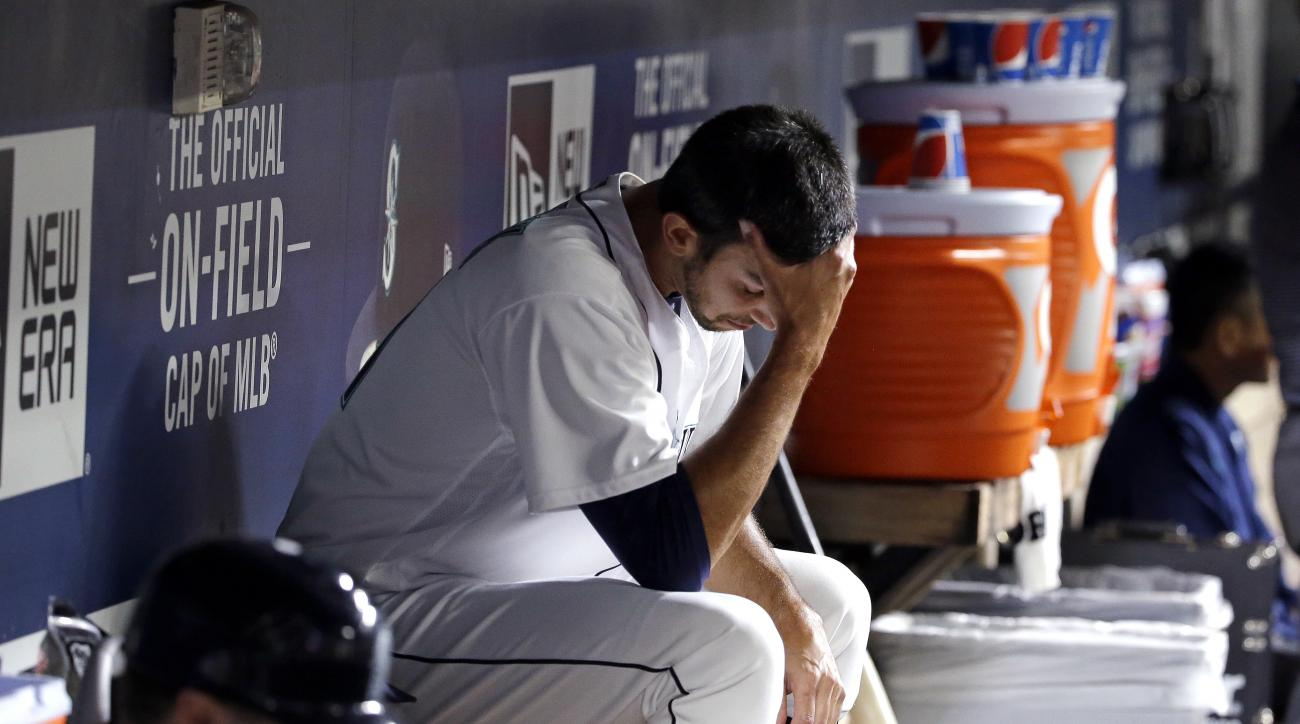 Seattle Mariners relief pitcher Steve Cishek looks down as he sits in the dugout after giving up a home run and being relieved in the ninth inning of a baseball game against the Boston Red Sox Monday, Aug. 1, 2016, in Seattle. (AP Photo/Elaine Thompson)