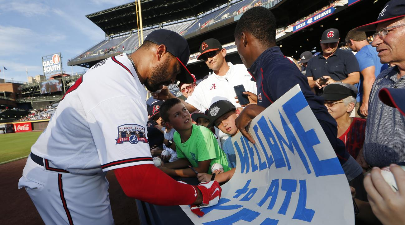 Atlanta Braves outfielder Matt Kemp gives an autograph before  a baseball game against the Pittsburgh Pirates, Tuesday, Aug. 2, 2016, in Atlanta. (AP Photo/John Bazemore)