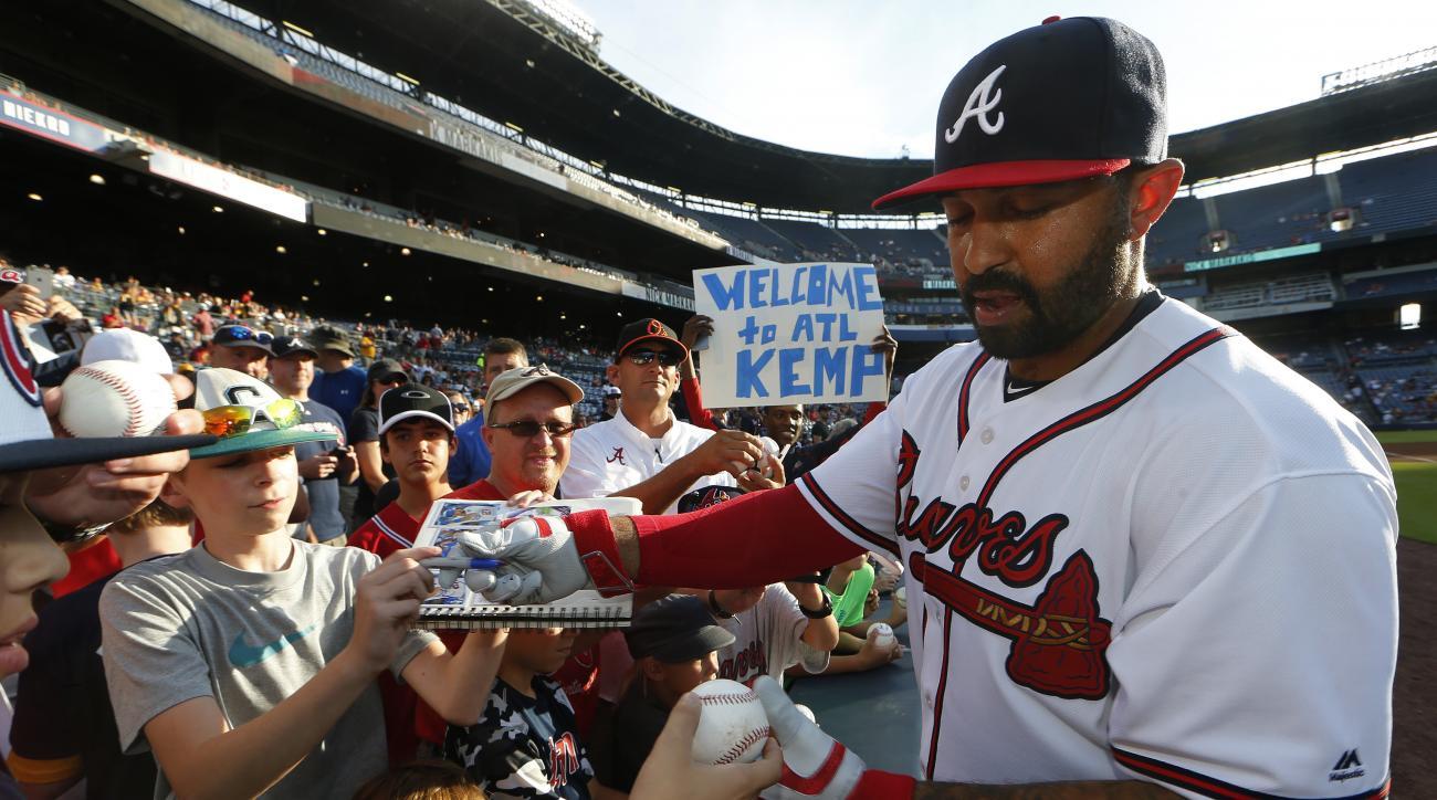 Newly aquired Atlanta Braves outfielder Matt Kemp gives utographs before his Atlanta debut in a baseball game against the Pittsburgh Pirates, Tuesday, Aug. 2, 2016, in Atlanta. (AP Photo/John Bazemore)