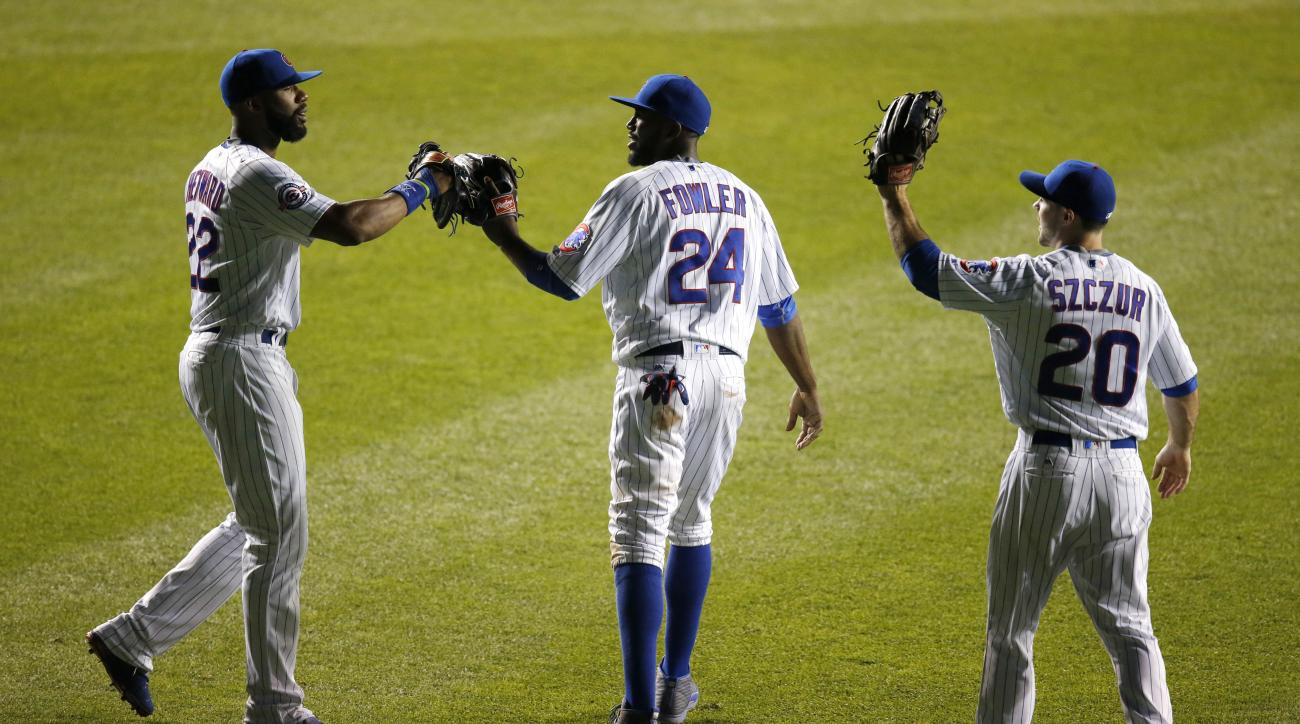 Chicago Cubs center fielder Dexter Fowler (24) celebrates the Cubs' 3-2 win over the Miami Marlins with teammates Jason Heyward (22) and Matt Szczur after the baseball game Tuesday, Aug. 2, 2016, in Chicago. (AP Photo/Charles Rex Arbogast)