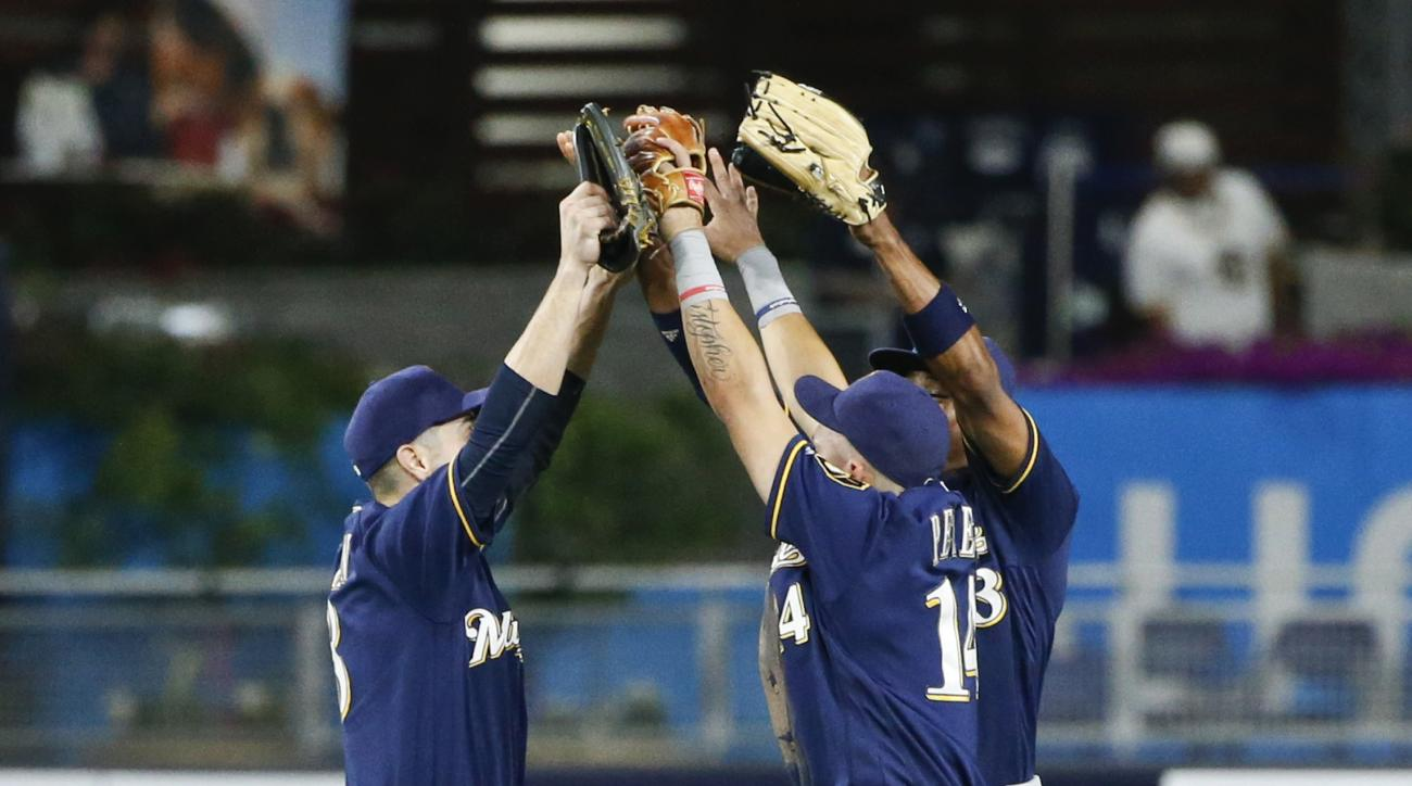 Milwaukee Brewers outfielders Ryan Braun, Hernan Perez, and Keon Broxton, from left, celebrate after the Brewers' 3-2 victory over the San Diego Padres in a baseball game Tuesday, Aug. 2, 2016, in San Diego. (AP Photo/Lenny Ignelzi)