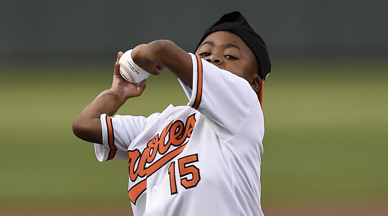Nine-year-old Zion Harvey, the world's first child to receive a bilateral hand transplant, throws out the first pitch before the Baltimore Orioles and Texas Rangers baseball in Baltimore, Tuesday, Aug. 2, 2016. Harvey, who lost his hands and feet to a ser