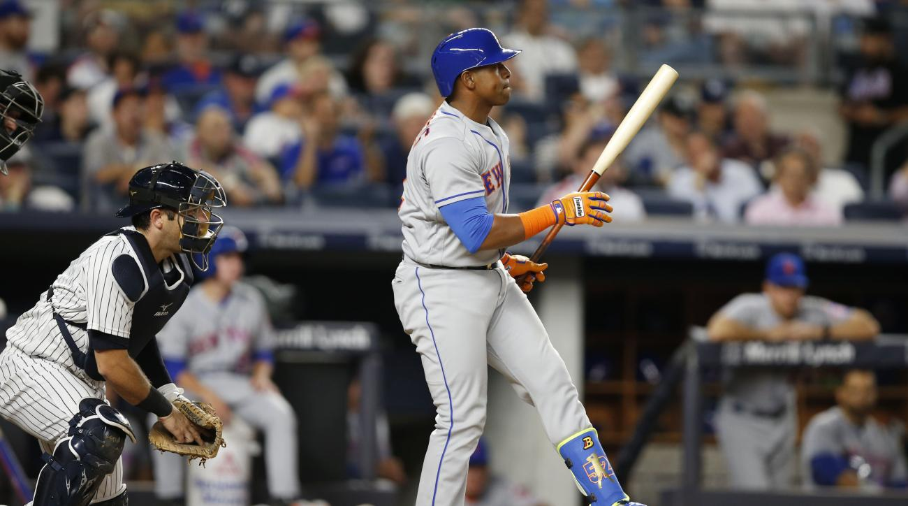 New York Mets' Yoenis Cespedes reacts after striking out swinging with two runners on base, next to New York Yankees catcher Austin Romine during the fourth inning of a baseball game, Wednesday, Aug. 3, 2016, in New York. (AP Photo/Kathy Willens)