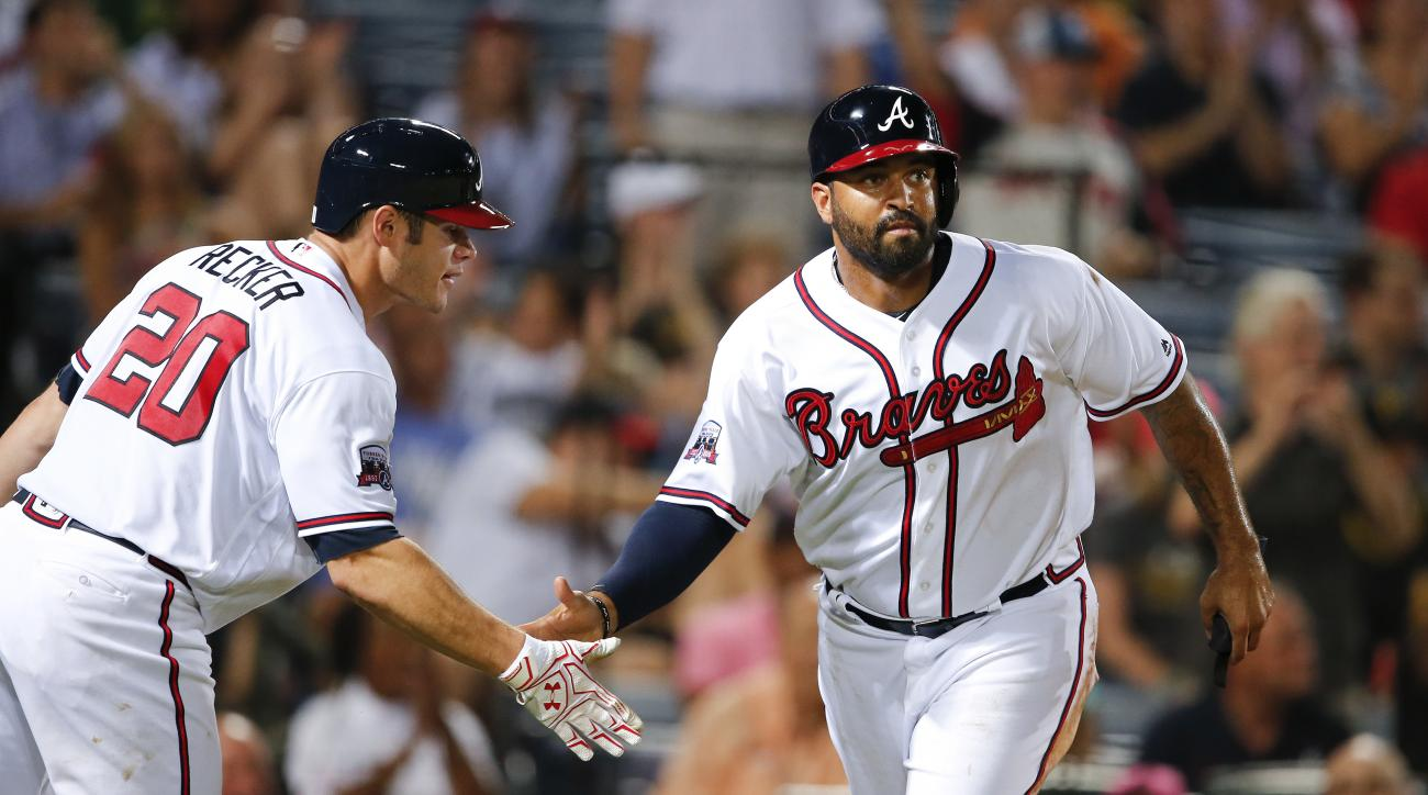 Atlanta Braves' Matt Kemp, right, celebrates with Anthony Recker after scoring on an Ender Inciarte base hit in the fifth inning of a baseball game against the Pittsburgh Pirates on Wednesday, Aug. 3, 2016, in Atlanta. (AP Photo/John Bazemore)