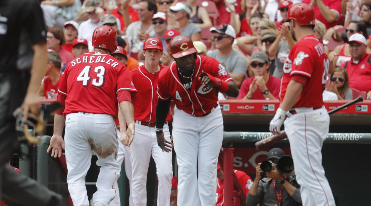 Cincinnati Reds' Brandon Phillips (4) celebrates after scoring with Scott Schebler (43) on a two-run single hit by Ramon Cabrera off St. Louis Cardinals starting pitcher Mike Leake in the second inning of a baseball game, Thursday, Aug. 4, 2016, in Cincin