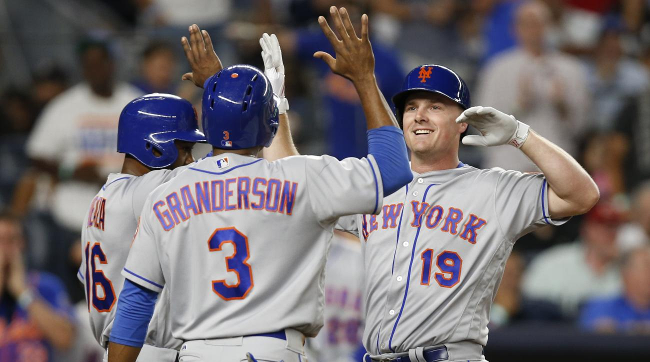 New York Mets' Alejandro de Aza, left, and Curtis Granderson (3) greet Jay Bruce (19) after they scored on Bruce's three-run home run during the fifth inning of a baseball game against the New York Yankees, Thursday, Aug. 4, 2016, in New York. (AP Photo/K