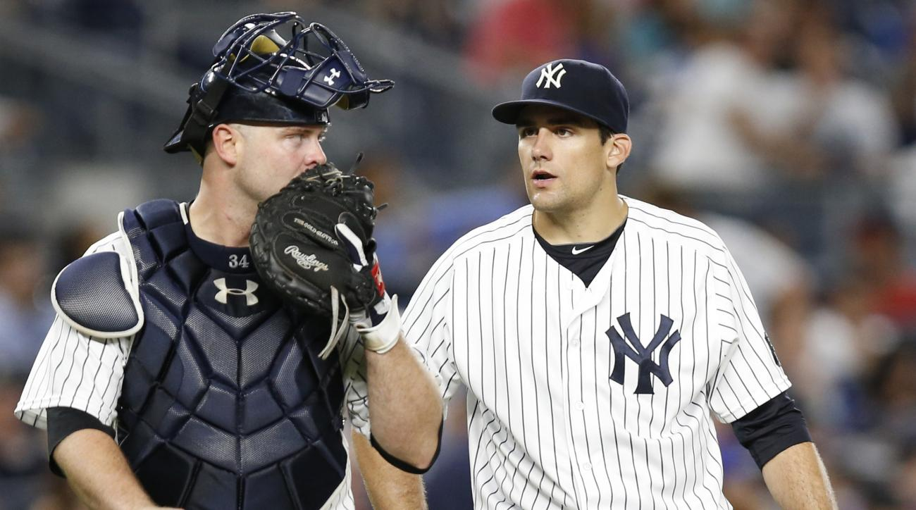 New York Yankees catcher Brian McCann, left, talks tostarting pitcher Nathan Eovaldi during the fifth inning of a baseball game against the New York Mets, Thursday, Aug. 4, 2016, in New York. Eovaldi gave up two home runs in the inning. (AP Photo/Kathy Wi