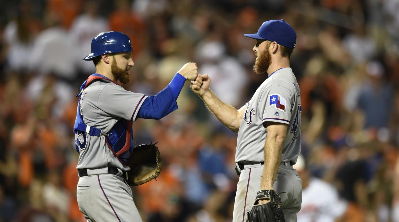 Texas Rangers pitcher Sam Dyson, right, and catcher Jonathan Lucroy celebrate the team's 5-3 win over the Baltimore Orioles in a baseball game, Thursday, Aug. 4, 2016, in Baltimore. (AP Photo/Gail Burton)