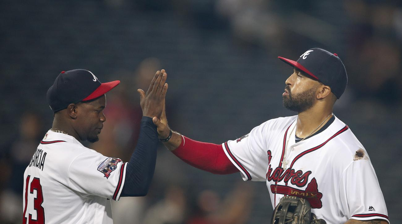 Atlanta Braves' Adonis Garcia, left and Matt Kemp celebrate after the Braves defeated the Pittsburgh Pirates 5-2 in a baseball game Thursday, Aug. 4, 2016, in Atlanta. (AP Photo/John Bazemore)